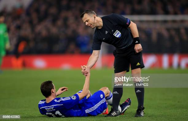 Chelsea's Nemanja Matic is helped up by referee Bjorn Kuipers