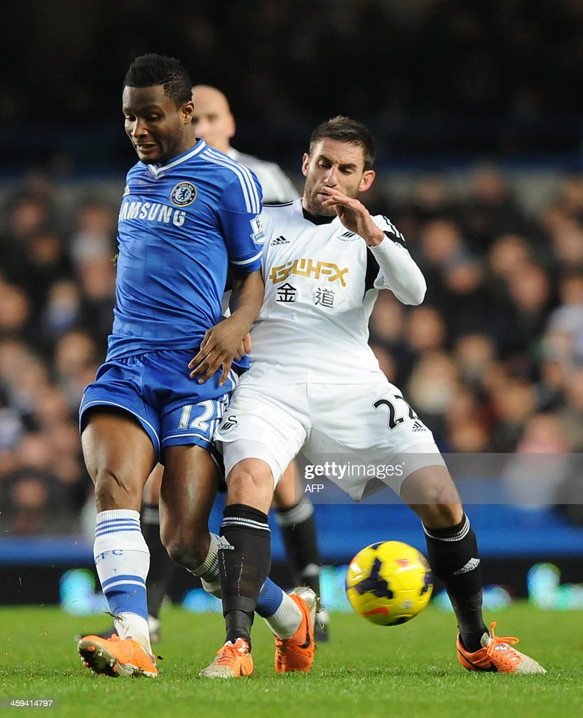 Chelsea's Nigerian midfielder John Obi Mikel (L) vies with Swansea City's Spanish defender Angel Rangel during the English Premier League football match between Chelsea and Swansea City at Stamford Bridge in London on December 26, 2013. Chelsea won the game 1-0. USE. No use with unauthorized audio, video, data, fixture lists, club/league logos or live services. Online in-match use limited to 45 images, no video emulation. No use in betting, games or single club/league/player publications.