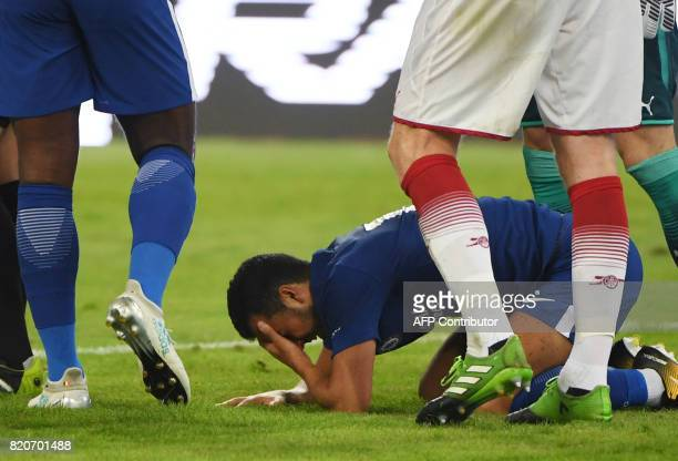 Chelsea's Pedro lies on the field after a collision with Arsenal's David Ospina during their preseason football match in Beijing's National Stadium...