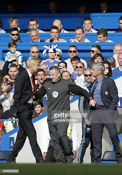 Chelsea's Portuguese manager Jose Mourinho and Arsenal's French manager Arsene Wenger are kept apart by the fourth official Jonathan Moss during the...