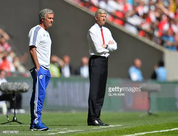 Chelsea's Portuguese manager Jose Mourinho and Arsenal's French manager Arsene Wenger watch from the side during the FA Community Shield football...