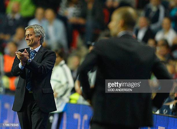 Chelsea's Portuguese manager Jose Mourinho applauds as he and Bayern Munich's Spanish head coach Pep Guardiola follow the action from the sideline...
