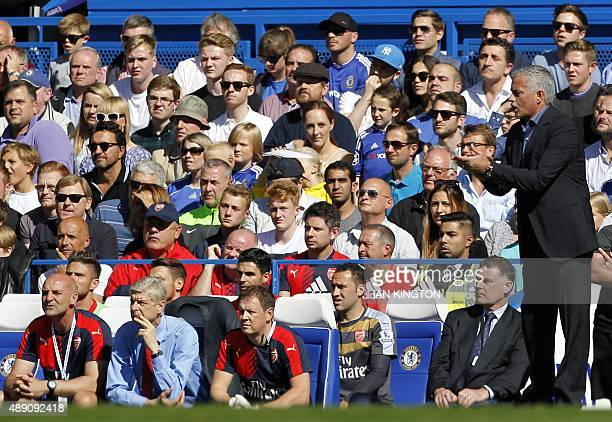 Chelsea's Portuguese manager Jose Mourinho gestures as Arsenal's French manager Arsene Wenger sits watching the English Premier League football match...