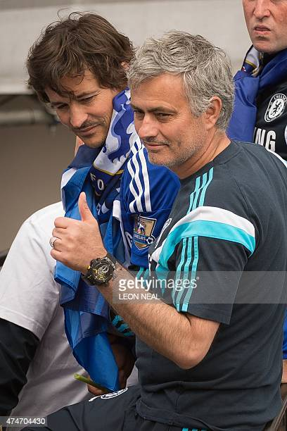 Chelsea's Portuguese manager Jose Mourinho gives a thumbs up as the Chelsea team take part in an opentop bus parade through Fulham southwest London...