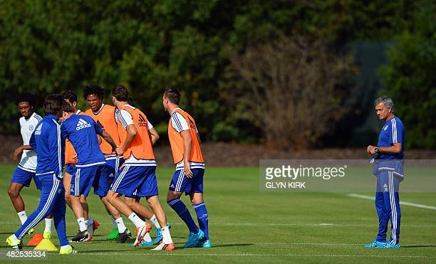 Chelsea's Portuguese manager Jose Mourinho watches his players during a team training session at Chelsea's training ground in Stoke D'Abernon south...