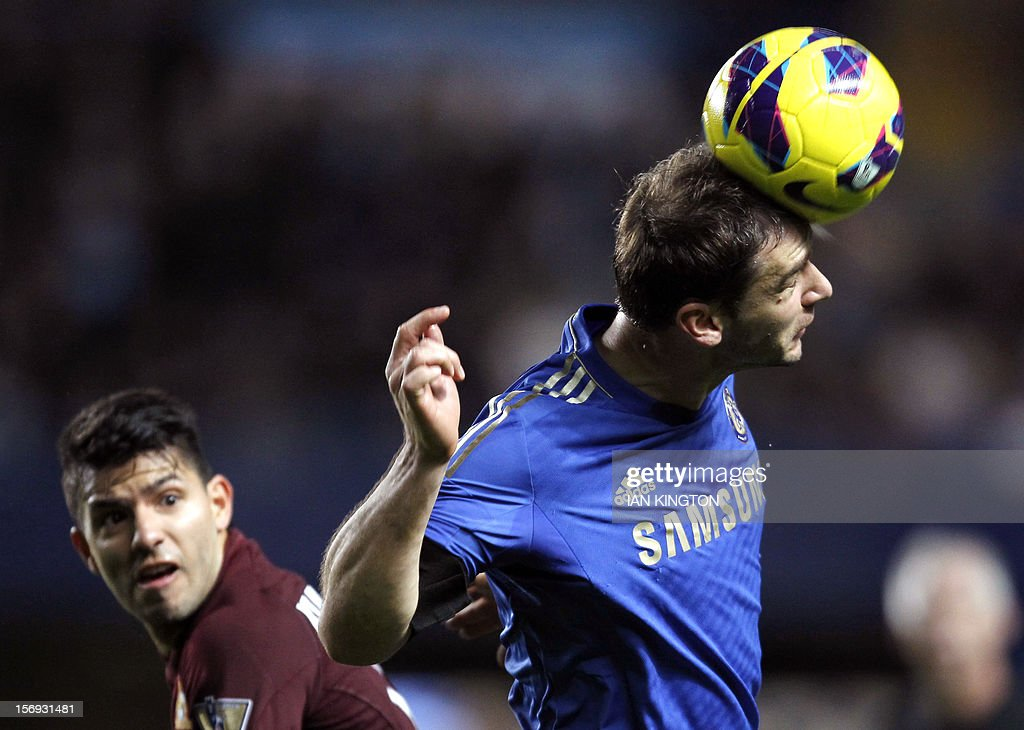 """Chelsea's Serbian defender Branislav Ivanovic (L) heads the ball as Manchester City's Argentinian striker Sergio Aguero looks on during the English Premier League football match between Chelsea and Manchester City at Stamford Bridge in London on November 25, 2012. USE. No use with unauthorized audio, video, data, fixture lists, club/league logos or """"live"""" services. Online in-match use limited to 45 images, no video emulation. No use in betting, games or single club/league/player publications"""