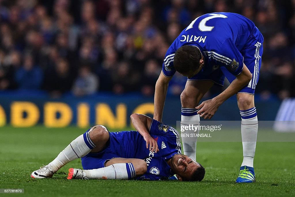 Chelsea's Serbian midfielder Nemanja Matic (R) checks on Chelsea's Spanish midfielder Pedro (L) who was clattered to the pitch by a late challenge from Tottenham Hotspur's English defender Kyle Walker that earned Walker a yellow card during the English Premier League football match between Chelsea and Tottenham Hotspur at Stamford Bridge in London on May 2, 2016. / AFP / BEN STANSALL / RESTRICTED TO EDITORIAL USE. No use with unauthorized audio, video, data, fixture lists, club/league logos or 'live' services. Online in-match use limited to 75 images, no video emulation. No use in betting, games or single club/league/player publications. /