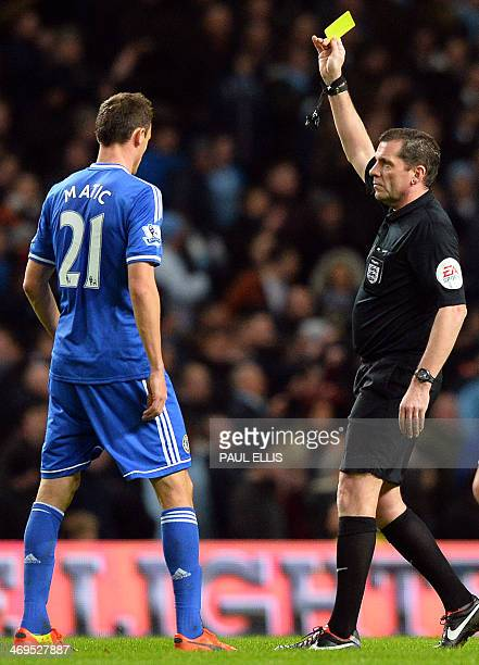 Chelsea's Serbian midfielder Nemanja Matic is shown a yellow card by referee Phil Dowd during the English FA Cup fifth round football match between...