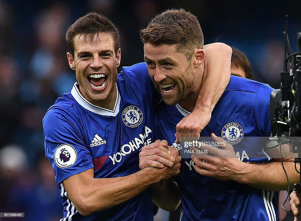 Chelsea's Spanish defender Cesar Azpilicueta (L) and Chelsea's English defender Gary Cahill celebrate following the English Premier League football match between Manchester City and Chelsea at the Etihad Stadium in Manchester, north west England, on December 3, 2016. Chelsea won the match 3-1. / AFP / Paul ELLIS / RESTRICTED TO EDITORIAL USE. No use with unauthorized audio, video, data, fixture lists, club/league logos or 'live' services. Online in-match use limited to 75 images, no video emulation. No use in betting, games or single club/league/player publications. /