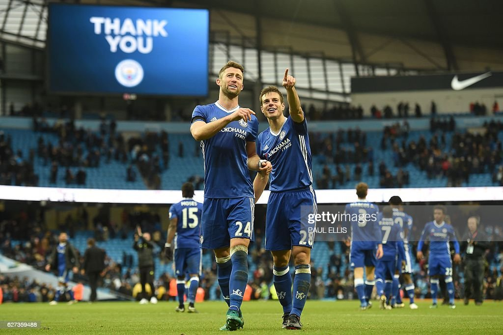 Chelsea's Spanish defender Cesar Azpilicueta (R) and Chelsea's English defender Gary Cahill celebrate following the English Premier League football match between Manchester City and Chelsea at the Etihad Stadium in Manchester, north west England, on December 3, 2016. Chelsea won the match 3-1. / AFP / Paul ELLIS / RESTRICTED TO EDITORIAL USE. No use with unauthorized audio, video, data, fixture lists, club/league logos or 'live' services. Online in-match use limited to 75 images, no video emulation. No use in betting, games or single club/league/player publications. /