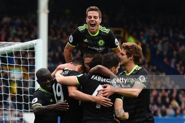 Chelsea's Spanish defender Cesar Azpilicueta jumps onto the celebration after Chelsea's Brazilian midfielder Willian scored their third goal during...