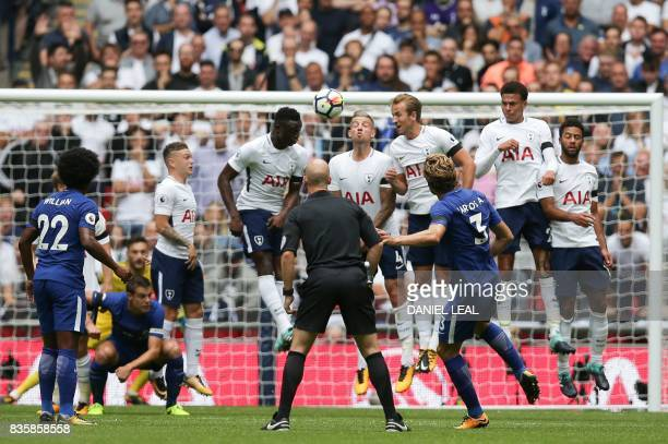 Chelsea's Spanish defender Marcos Alonso curls a free kick over the Tottenham defensive wall to score the opening goal during the English Premier...