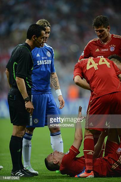 Chelsea's Spanish forward Fernando Torres Bayern Munich's French midfielder Franck Ribery reacts as he lies on the ground while being helped by...