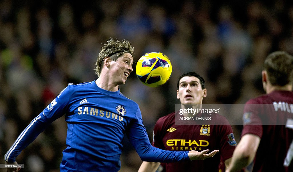 """Chelsea's Spanish forward Fernando Torres (L) heads the ball as Manchester City's English midfielder Gareth Barry (2nd R) looks on during the English Premier League football match between Chelsea and Manchester City at Stamford Bridge stadium in London on November 25, 2012. AFP PHOTO/ADRIAN DENNIS USE. No use with unauthorized audio, video, data, fixture lists, club/league logos or """"live"""" services. Online in-match use limited to 45 images, no video emulation. No use in betting, games or single club/league/player publications"""