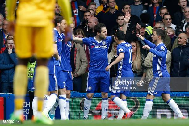 Chelsea's Spanish midfielder Cesc Fabregas celebrates with teammates after scoring the opening goal of the English Premier League football match...