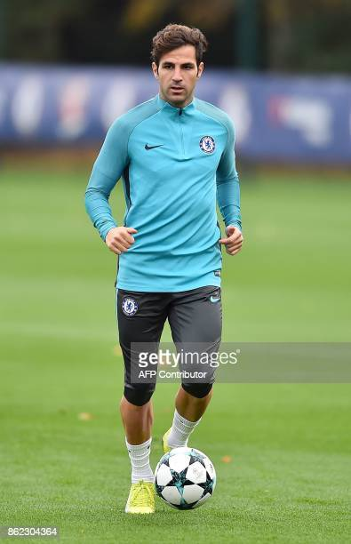 Chelsea's Spanish midfielder Cesc Fabregas runs with the ball during a team training session at Chelsea's Cobham training facility in Stoke D'Abernon...