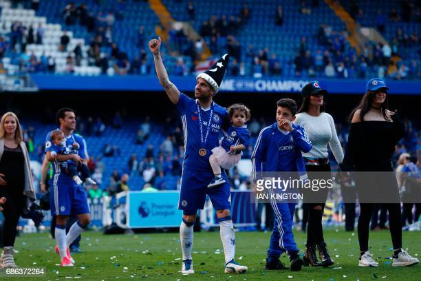Chelsea's Spanish midfielder Cesc Fabregas salutes the crowd at the end of the presentation ceremony for the English Premier League trophy at the end...