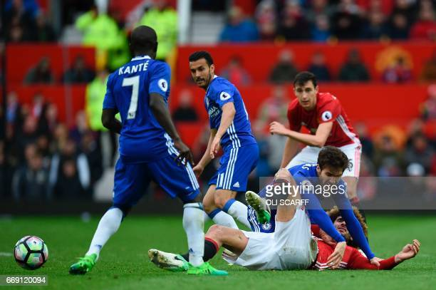 Chelsea's Spanish midfielder Cesc Fabregas tangles on the floor with Manchester United's Belgian midfielder Marouane Fellaini during the English...