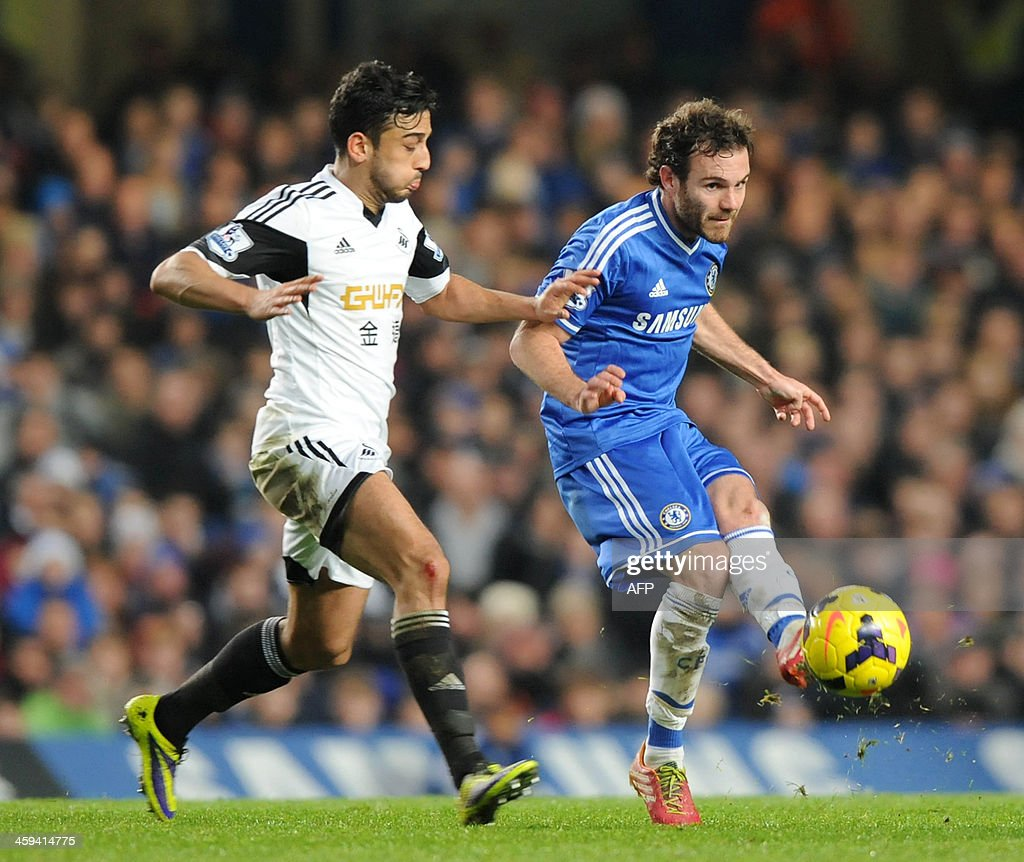 Chelsea's Spanish midfielder Juan Mata (L) vies with Swansea City's Welsh defender Neil Taylor (L) during the English Premier League football match between Chelsea and Swansea City at Stamford Bridge in London on December 26, 2013. Chelsea won the game 1-0. AFP PHOTO / OLLY GREENWOOD USE. No use with unauthorized audio, video, data, fixture lists, club/league logos or live services. Online in-match use limited to 45 images, no video emulation. No use in betting, games or single club/league/player publications.