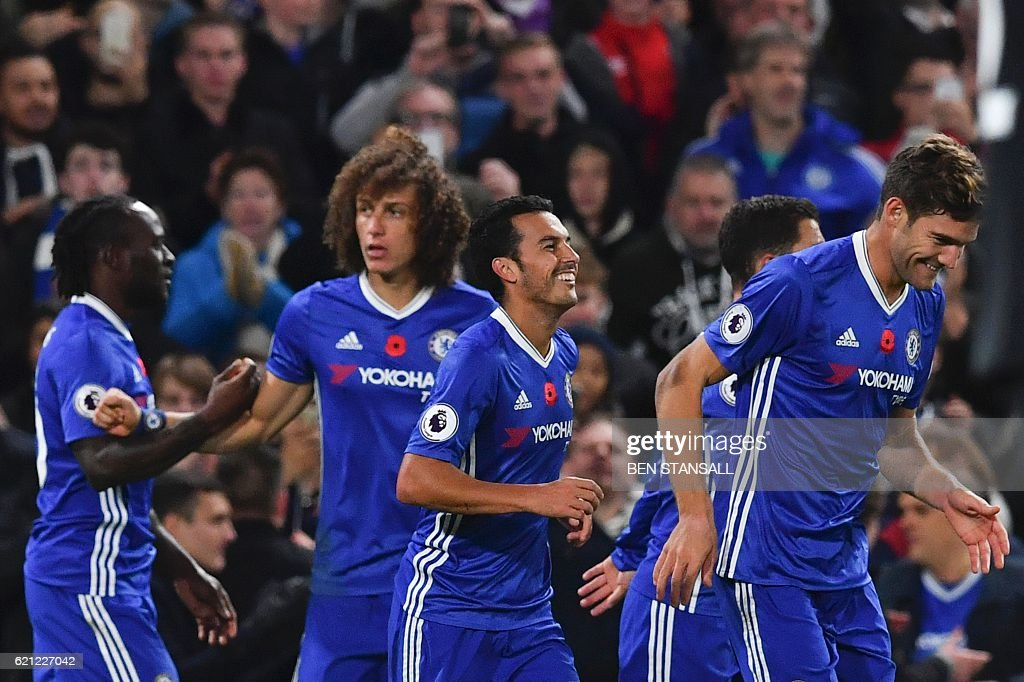Chelsea's Spanish midfielder Pedro (C) celebrates with teammates after scoring their fifth goal during the English Premier League football match between Chelsea and Everton at Stamford Bridge in London on November 5, 2016. / AFP / Ben STANSALL / RESTRICTED TO EDITORIAL USE. No use with unauthorized audio, video, data, fixture lists, club/league logos or 'live' services. Online in-match use limited to 75 images, no video emulation. No use in betting, games or single club/league/player publications. /