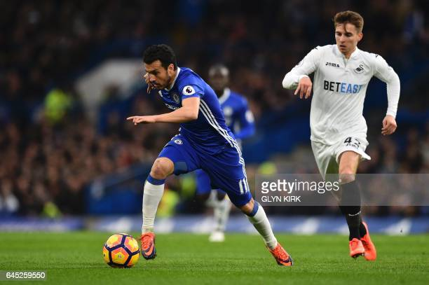 Chelsea's Spanish midfielder Pedro runs with the ball pursued by Swansea City's English midfielder Tom Carroll during the English Premier League...