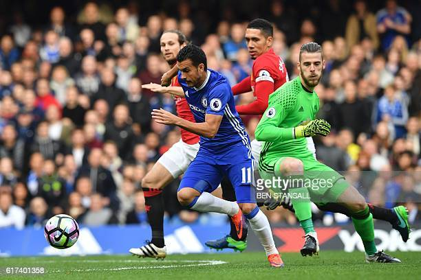 Chelsea's Spanish midfielder Pedro takes the ball around Manchester United's Spanish goalkeeper David de Gea on his way to scoring the opening goal...