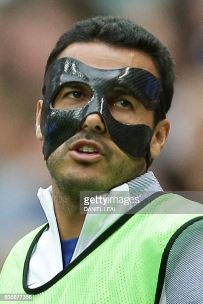 Chelsea's Spanish midfielder Pedro warms up with a mask protecting his face during the English Premier League football match between Tottenham...