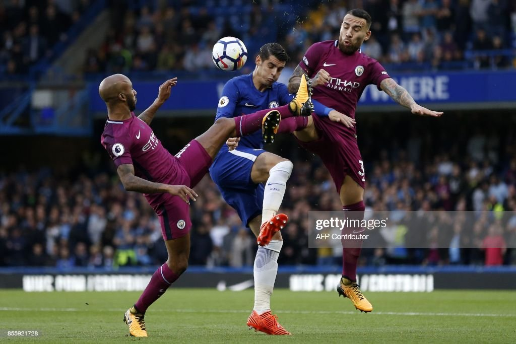 Chelsea's Spanish striker Alvaro Morata (C) vies with Manchester City's English midfielder Fabian Delph (L) and Manchester City's Argentinian defender Nicolas Otamendi (R) during the English Premier League football match between Chelsea and Manchester City at Stamford Bridge in London on September 30, 2017. / AFP PHOTO / Ian KINGTON / RESTRICTED TO EDITORIAL USE. No use with unauthorized audio, video, data, fixture lists, club/league logos or 'live' services. Online in-match use limited to 75 images, no video emulation. No use in betting, games or single club/league/player publications. /