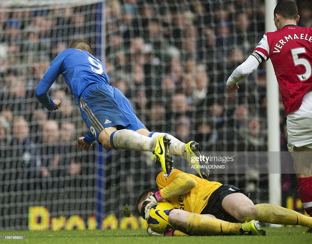 "Chelsea's Spanish striker Fernando Torres (L) goes over Arsenal's Polish goalkeeper Wojciech Szczesny (C) during the English Premier League football match between Chelsea and Arsenal at Stamford Bridge in London on January 20, 2013. Chelsea won the game 2-1. AFP PHOTO / ADRIAN DENNIS USE. No use with unauthorized audio, video, data, fixture lists, club/league logos or ""live"" services. Online in-match use limited to 45 images, no video emulation. No use in betting, games or single club/league/player publications."