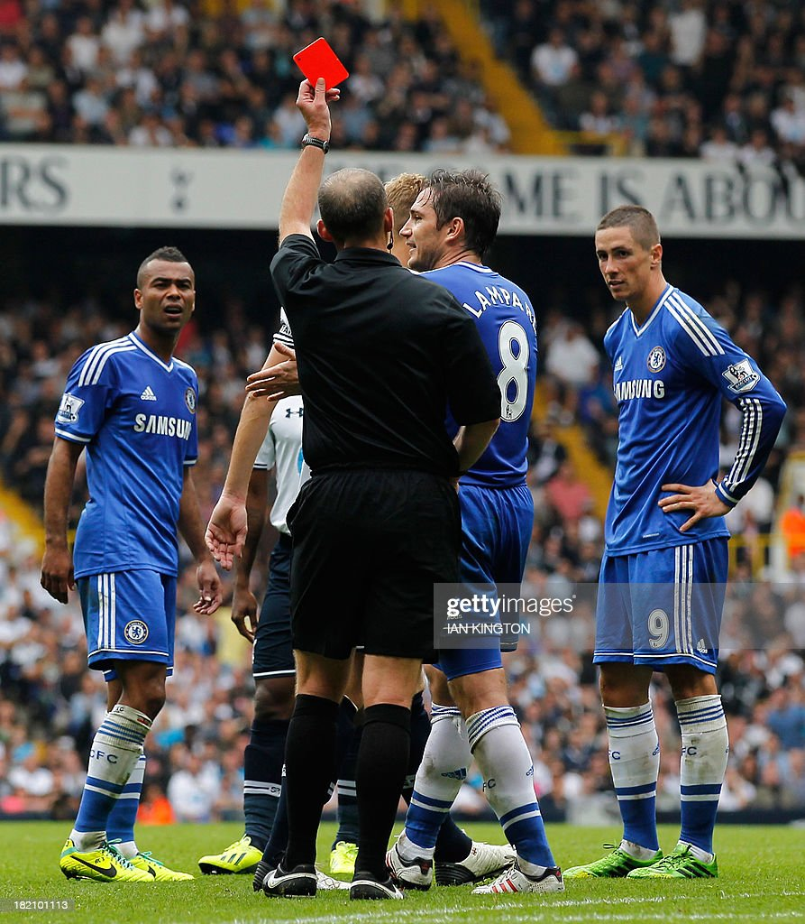 Chelsea's Spanish striker Fernando Torres (R) is shown the red card by referee Mike Dean for a second bookable offence as Chelsea's English defender Ashley Cole (L) reacts during the English Premier League football match between Tottenham Hotspur and Chelsea at White Hart Lane in London on September 28, 2013. AFP PHOTO/ IAN KINGTON PUBLICATIONS