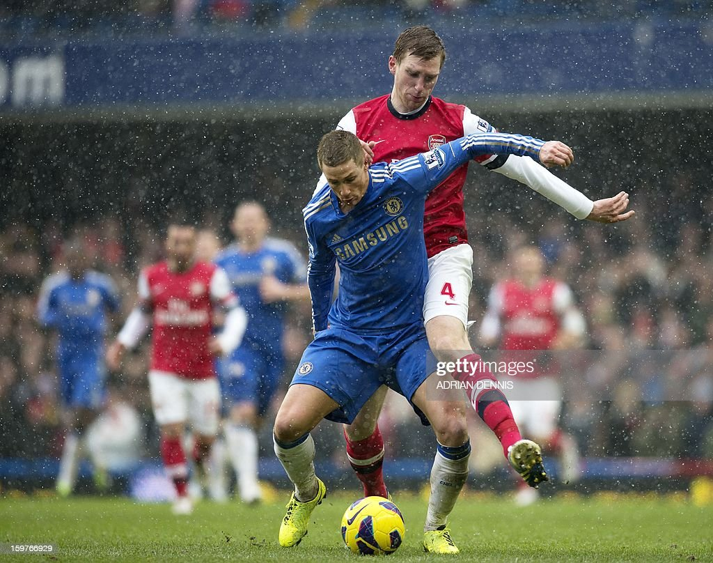 "Chelsea's Spanish striker Fernando Torres (L) vies for the ball against Arsenal's German defender Per Mertesacker (R) during the English Premier League football match between Chelsea and Arsenal at Stamford Bridge in London on January 20, 2013. Chelsea won the game 2-1. USE. No use with unauthorized audio, video, data, fixture lists, club/league logos or ""live"" services. Online in-match use limited to 45 images, no video emulation. No use in betting, games or single club/league/player publications."