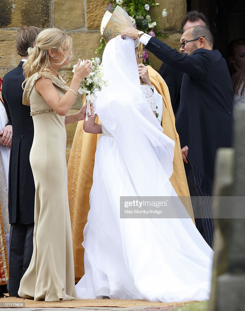 Chelsy Davy looks on as Bruce Oldfield adjusts Lady Melissa Percy's wedding dress as she arrives at St Michael's Church for her wedding on June 22, 2013 in Alnwick, England.