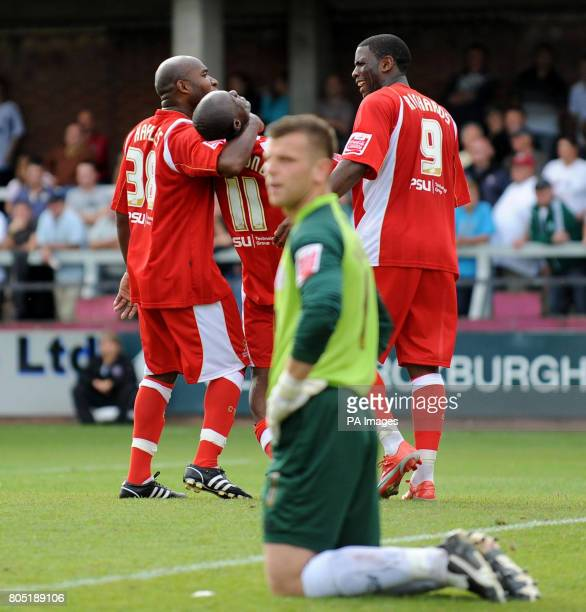 Cheltenham Town's Elvis Hammond celebrates his goal with Barry Hayles and Justin Richards as Hereford United goalkeeper Adam Bartlett looks dejected...