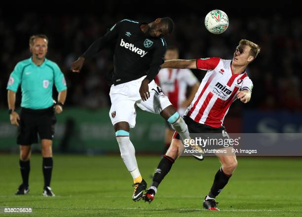 Cheltenham Town's Kyle Storer and West Ham United's Pedro Mba Obiang battle for the ball during the Carabao Cup Second Round match at the LCI Rail...