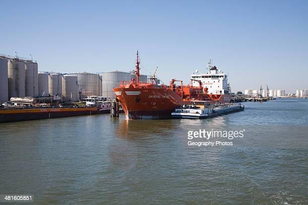 Chemical oil bulk carrier ship Crystal Topaz next to storage tanks Port of Rotterdam Netherlands
