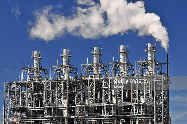 A chemical plant with smoke rising against a blue sky