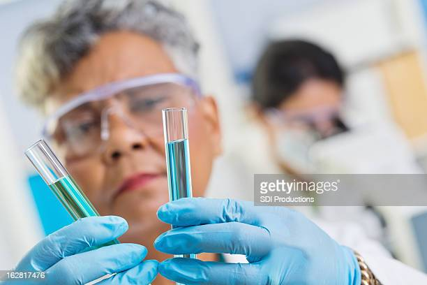 chemist combining chemicals in test tubes at science lab