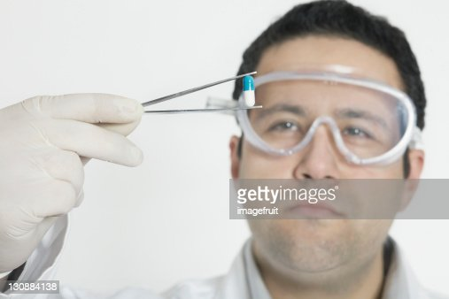 Chemist holding pill with tweezers