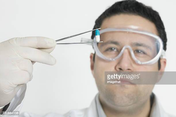 Chemist holding pill with tweezers