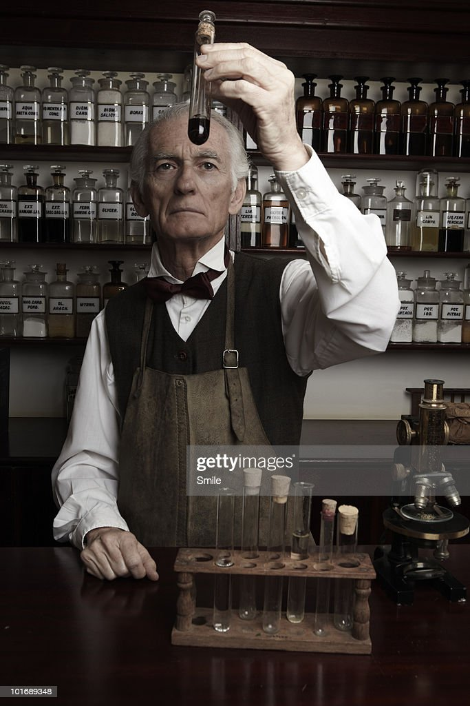 Chemist inspecting a test tube : Stock Photo