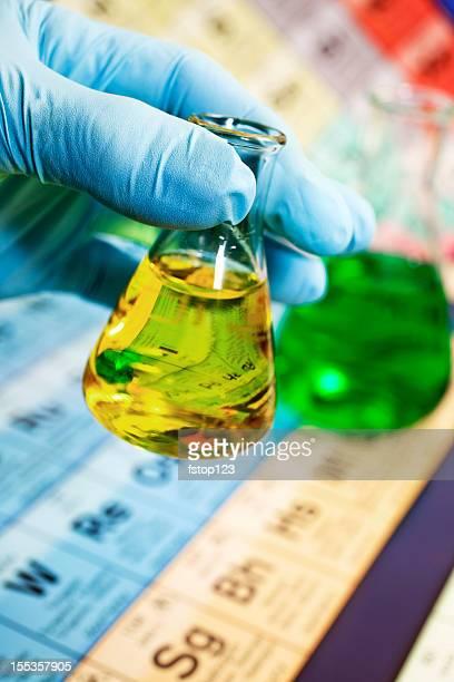Chemiker Tragen von Handschuhen hältst eine Glaskolben