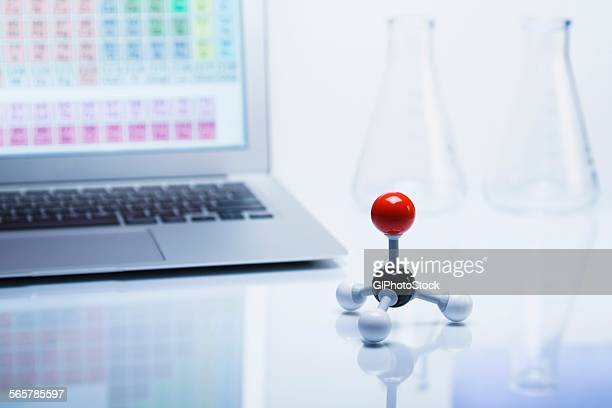 Chemistry research. Ball-and-stick molecular model with laptop computer displaying periodic table