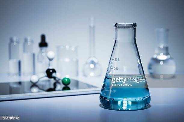 Chemistry research. Erlenmeyer flask containing colored liquid and a digital tablet with a ball-and-stick molecular model on its screen
