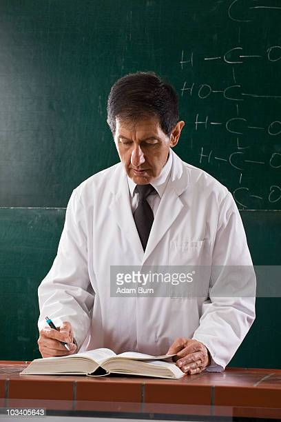 A chemistry teacher consulting a textbook in his classroom