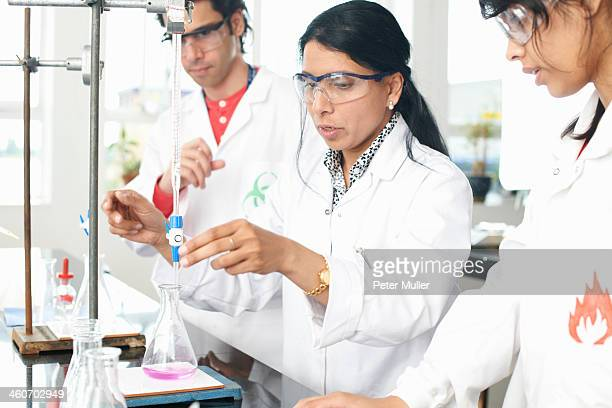 Chemistry teacher doing experiment with students