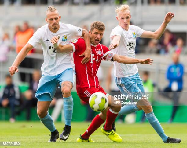 Chemnitz's defender Maurice Trapp and Tom Scheffel and Munich's forward Thomas Mueller vie for the ball during the German football Cup DFB Pokal...
