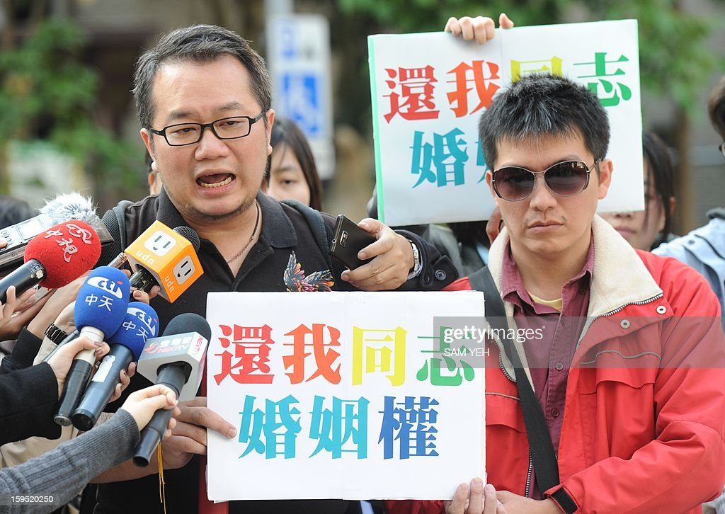 Chen Ching-hsueh (L) and his partner Kao Chih-wei display placards reading ' return my marriage rights ' outside the Taipei High Administrative Court on January 15, 2013. Chen said he received death threats after he went public with his appeal against the government in the Taipei High Administrative Court to register his 'marriage' with his gay partner. The court did not make a final decision in a hearing on January 15 on whether to submit Chen's case to the Grand Justices to allow time for both sides to present additional arguments. AFP PHOTO / Sam Yeh