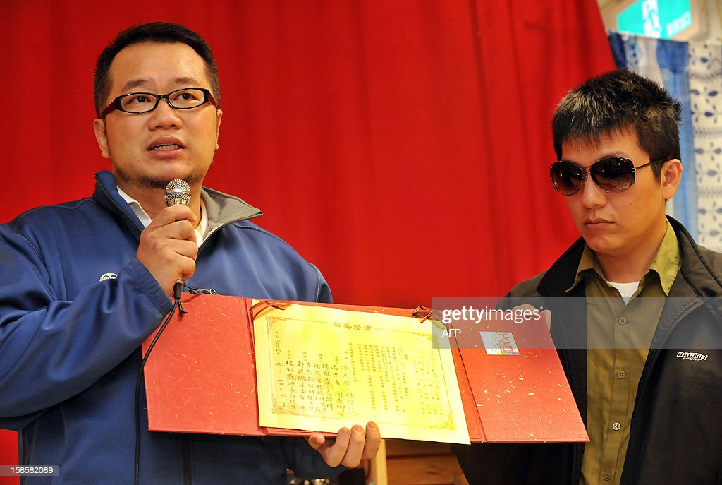 Chen Ching-hsueh (L) and his partner Kao Chih-wei display their wedding certificate during a press conference in Taipei on December 20, 2012. A Taiwan court shrank away from ruling on the gay couple's wish to have their marriage registered, saying it would pass on the controversial case to the island's top judicial body. Chen and his partner Kao earlier this year filed a complaint with the administrative court against a local household registration agency which turned them away when they tried to register their marriage. AFP PHOTO / Mandy CHENG