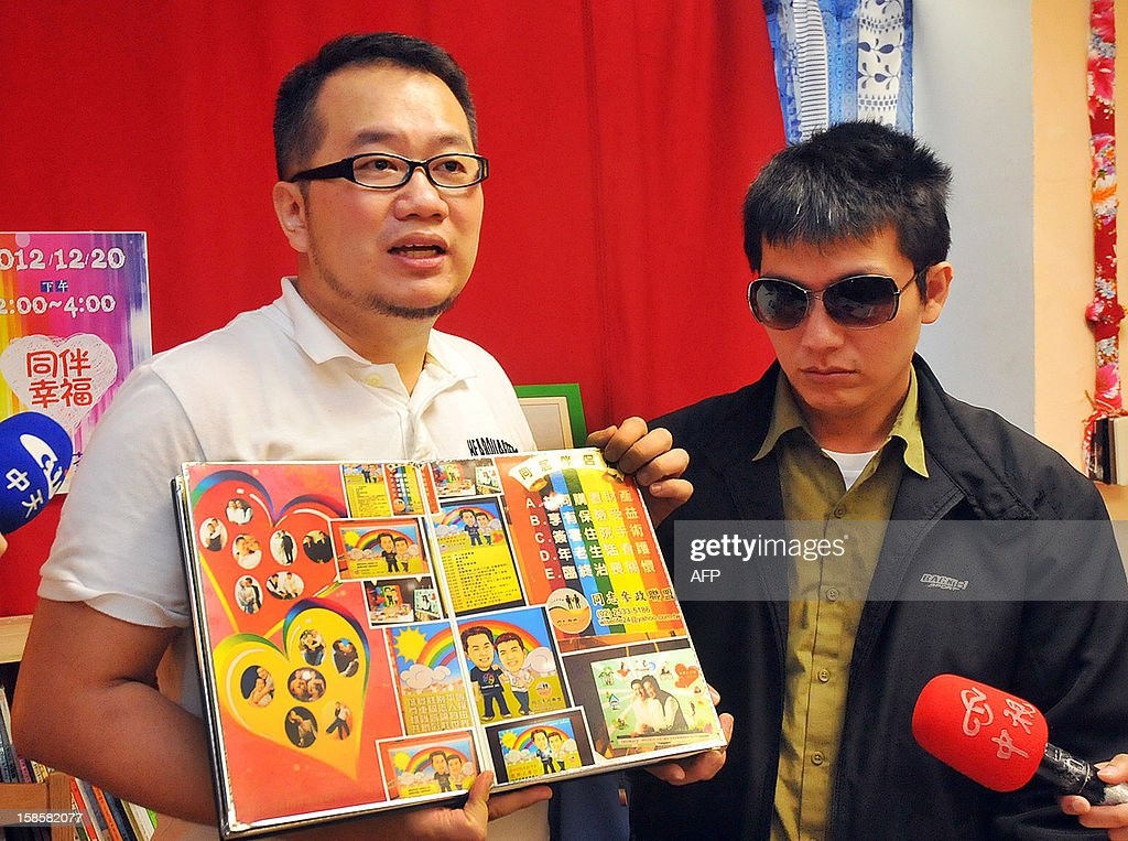 Chen Ching-hsueh (L) and his partner Kao Chih-wei display their wedding photo album during a press conference in Taipei on December 20, 2012. A Taiwan court shrank away from ruling on the gay couple's wish to have their marriage registered, saying it would pass on the controversial case to the island's top judicial body. Chen and his partner Kao earlier this year filed a complaint with the administrative court against a local household registration agency which turned them away when they tried to register their marriage. AFP PHOTO / Mandy CHENG