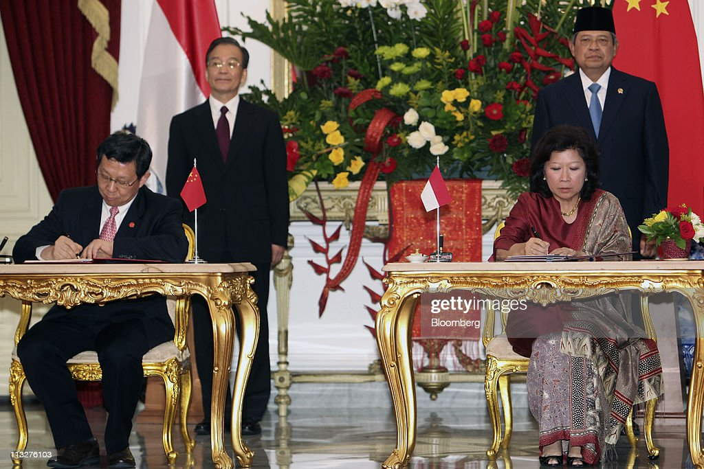 Chen Deming, China's minister of commerce, seated at left, and <a gi-track='captionPersonalityLinkClicked' href=/galleries/search?phrase=Mari+Elka+Pangestu&family=editorial&specificpeople=861618 ng-click='$event.stopPropagation()'>Mari Elka Pangestu</a>, Indonesia's minister of trade sign agreements in Jakarta, Indonesia, on Friday, April 29, 2011. Looking on are <a gi-track='captionPersonalityLinkClicked' href=/galleries/search?phrase=Wen+Jiabao&family=editorial&specificpeople=204598 ng-click='$event.stopPropagation()'>Wen Jiabao</a>, China's premier, standing at center left, and <a gi-track='captionPersonalityLinkClicked' href=/galleries/search?phrase=Susilo+Bambang+Yudhoyono&family=editorial&specificpeople=206513 ng-click='$event.stopPropagation()'>Susilo Bambang Yudhoyono</a>, Indonesia's president, right. Photographer: Dimas Ardian/Bloomberg via Getty Images